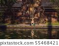 Woman feeding beautiful coloured fish in pond temple on Bali 55468421