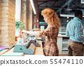 Woman wearing squared dress using printer near window 55474110
