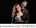 Portrait of young man dressed up like Dracula looking at the neck of his vampire woman 55482925