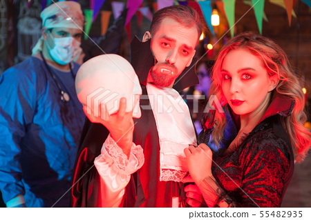 Attractive young man dressed up like Dracula with his beautiful girl for halloween party 55482935