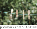 wooden clothes pegs hanged on rope at garden 55484140