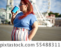 Fat and young woman drink coffee on street 55488311
