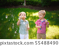 two happy boy play in bubbles outdoors 55488490