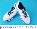 Pair of male white sneakers on a blue background 55491514