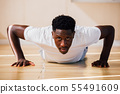 Portrait of young African American man doing push-up on the floor 55491609