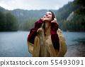 woman in raincoat near lake in rainy day. 55493091