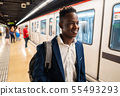 African American businessman wearing blue suit and backpack 55493293