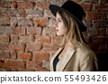 style girl in hat and clothes on a brick wall background 55493426