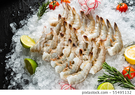 raw shrimps with lime and rosemary on the ice 55495132