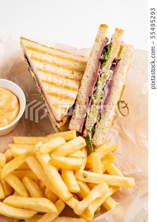 Club Sandwich with Cheese, PIckled Cucmber, Tomato and Smoked Meat. Garnished with French Fries 55495293