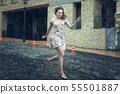 Young woman runs in the rain. 55501887