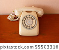 A retro telephone on wood table.  55503316