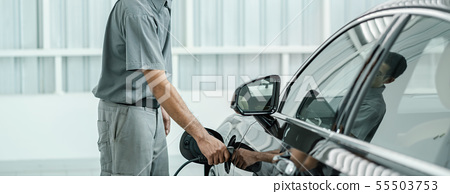 Senior asian Technician is charging the electric car or EV in service center for maintainance, Eco-friendly alternative energy concept 55503753