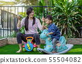 Asian single mom with son are playing with toy and eating together when living in Front lawn of modern house for Self learning or home school, Family and single mom concept, selective focus 55504082