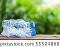 Clear empty plastic bottle on wooden table or counter with green nature light blur background 55504868