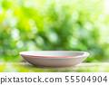 White empty ceramic dish on wooden table with green blur light background. For photo montage 55504904