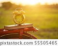 Yellow alarm clock and book put on the Red Japan style classic bicycle 55505465