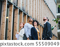 Group of young businesspeople standing outdoors in courtyard, looking up. 55509049