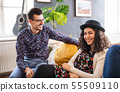 Young friends sitting on sofa indoors, talking. 55509110