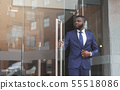 Confident african businessman walking out of modern office center 55518086