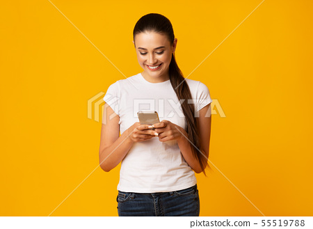 Smiling Lady Using Cellphone On Yellow Studio Background 55519788