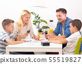 Happy young family playing card game at dining table at bright modern home. 55519827
