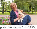 Active senior woman with dog on a walk  55524358