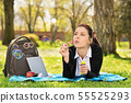 Young girl lying on a meadow blowing soap bubbles 55525293