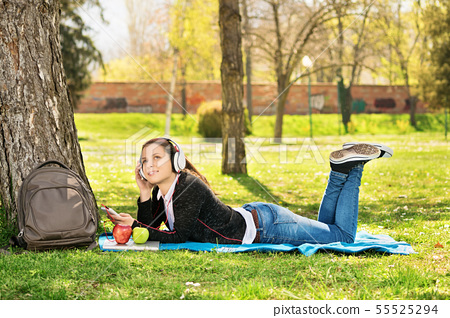 Young girl listening to music in the park 55525294