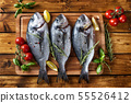 Top view of three raw dorado fishes on brown 55526412