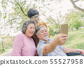 senior Asian man using smartphone for selfie with 55527958