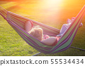 Beautiful girl resting in a hammock at sunset. 55534434