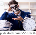 Businessmsn with scary face mask working in office 55538636