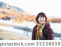 An older lady smiling while looking at the Winter 55538939