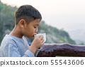 Asian kid boy is drinking water from the glass. 55543606