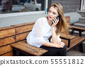 Charming woman with a beautiful smile speaks good news on a mobile phone while relaxing in a cafe, a 55551812