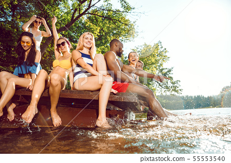 splashing water and laughting on the pier on river 55553540
