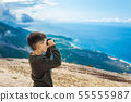 Young boy at mountain top looking through binoculars 55555987