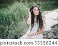 Woman in boho dress posing near lake. 55556244