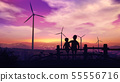 Two boys at sunset look at wind turbines 55556716