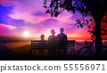 Family rests on a bench under the tree and watches sunset over the river 55556971