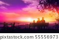 Family of three on a bench at sunset and a beautiful view of the river 55556973