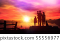 Family with children watching at the setting sun in the countryside 55556977