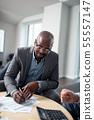 Dark-skinned man signing documents sitting near tax lawyer 55557147