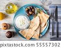 tzatziki with pita bread on blue plate 55557302
