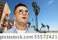 surprised man in sunglasses over venice beach 55572421