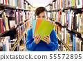shy student boy hiding behind books at library 55572895