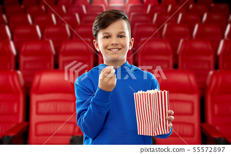 happy smiling boy eating popcorn at movie theater 55572897