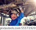 mechanic man with flashlight repairing car at shop 55572920