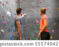man and woman exercising at indoor climbing gym 55574042